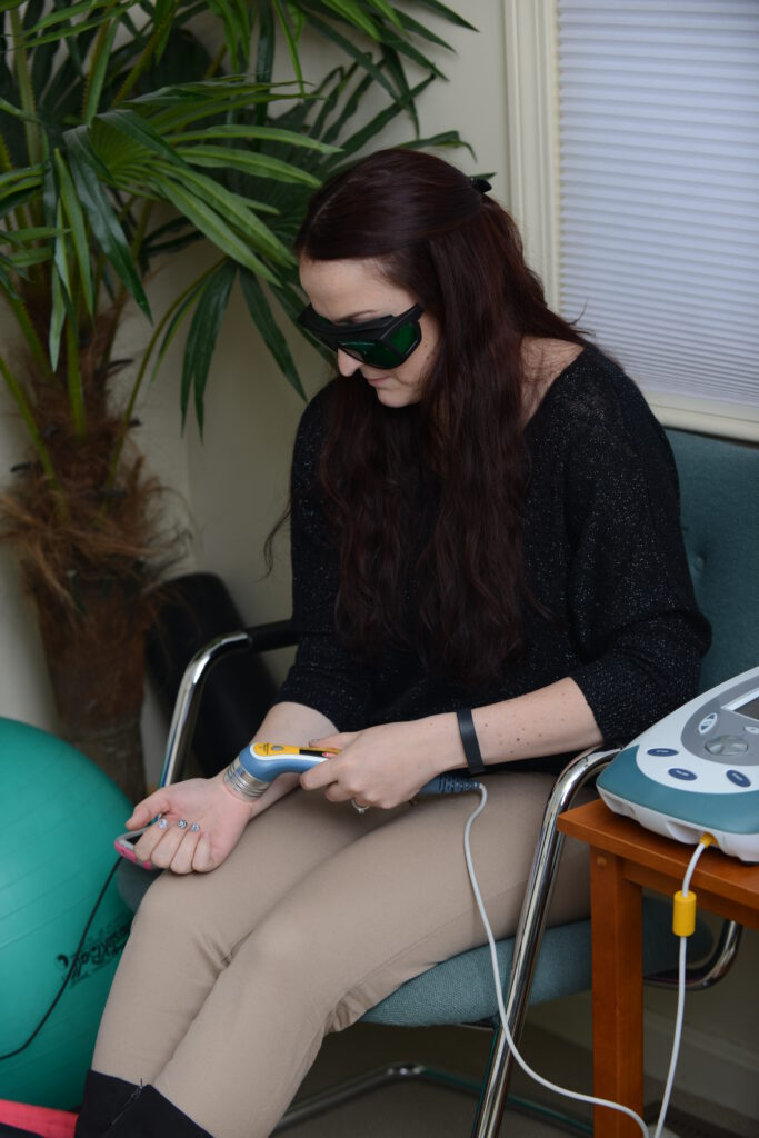 Lady Administering Cold Laser Therapy Nashua Chiropractor